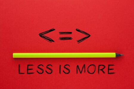 Less is more phrase and pencil on red background. Business concept. Stockfoto