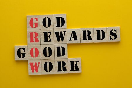GROW acronym with conceptual words god, reward, good and work in wooden blocks on yellow background.