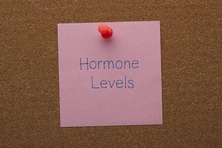 Hormone levels written on note pinned on cork board.