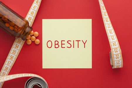 The word obesity written on note with weight loss pills and tape measure.