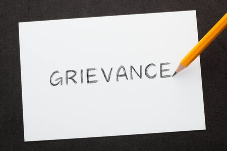 The word grievance written with pencil on  white sheet. Business Concept