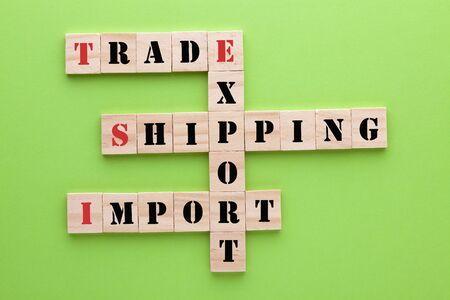 Words trade, export, import and shipping concept crossword clues in wooden blocks on green background.