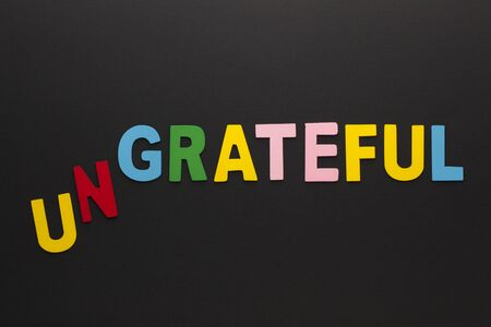 The word ungrateful transformed to grateful made of colorful alphabet letters on black background.