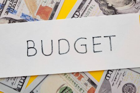 The word budget written on white paper sheet with hundred dollar bills. Business concept. Stockfoto