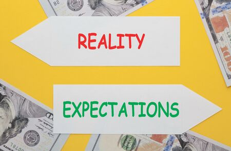 The words Reality vs Expectations written on paper arrow with hundred dollar bills. Business concept.