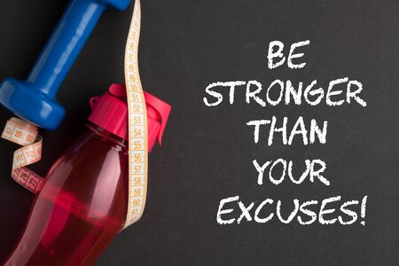 Be stronger than your excuses text with dumbbell, measuring tape and water bottle. Concept sport, diet, fitness.