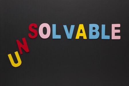 The word unsolvable transformed to solvable made of colorful alphabet letters on black background. Foto de archivo