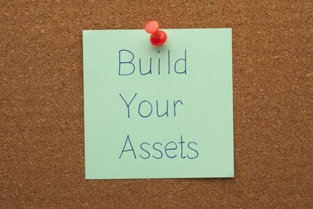 Build Your Assets handwritten note pinned on cork board.