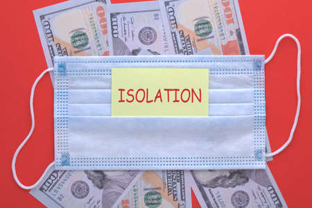 The word isolation written on sticker with medical mask and  hundred dollar bills. The concept of epidemic
