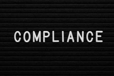 The word compliance on letter board. Business concept