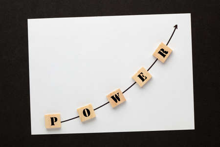 The word power with directional arrow written on cubes shape wooden blocks.