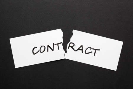 The word contract on torn paper in black background.