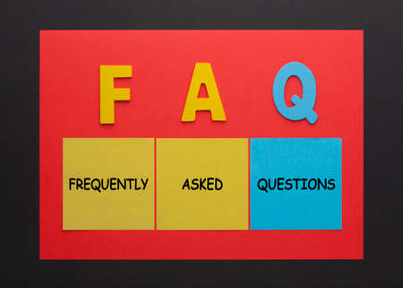 Acronym of FAQ - Frequently Asked Questions written on a note. 免版税图像