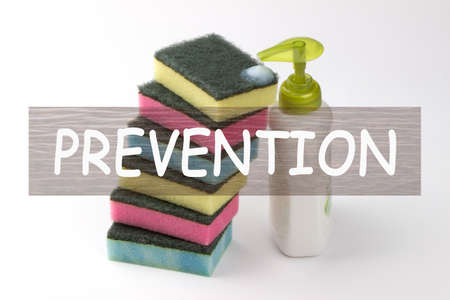 The word prevention on kitchen sponge with a detergent background.