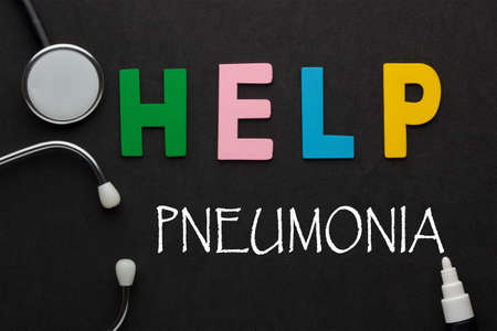 Help pneumonia text with stethoscope on black background. Concept of medical and health care. 免版税图像