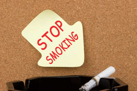 Stop smoking text on on sticky note and cigarette