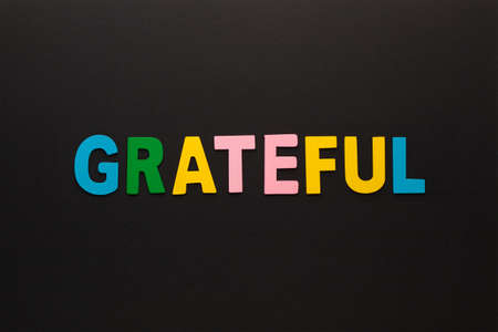 The word grateful made of colorful alphabet letters on black background.