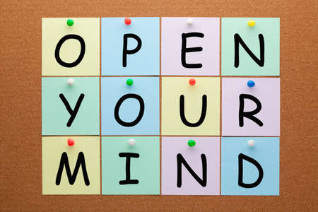 Open your mind text on notes pinned on cork board.