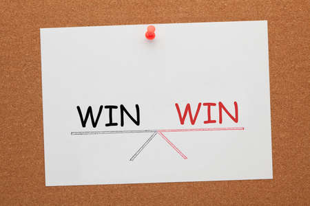 Win and win balance on seesaw drawing on white paper sheet pinned on cork board.