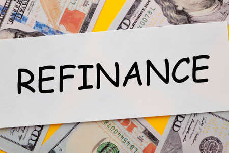 The word Refinance written on white paper sheet with hundred dollar bills. Business concept.