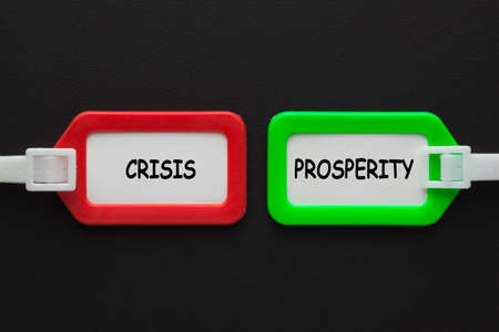 The words Crisis or Prosperity in luggage tags on black background. Business concept. 免版税图像