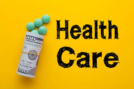 The word health care with medical pills with rolled 100 dollar banknotes on a yellow background.