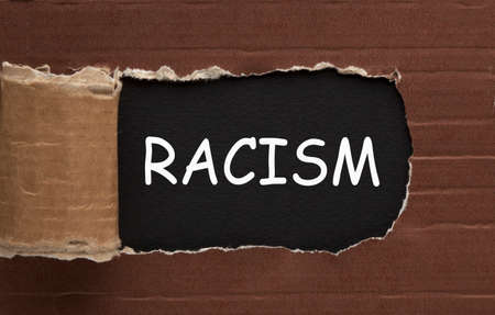 The word racism under torn paper. Business concept