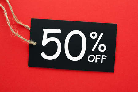 50% off discount promotion sale concept on black tag hanging on a rope on red background.