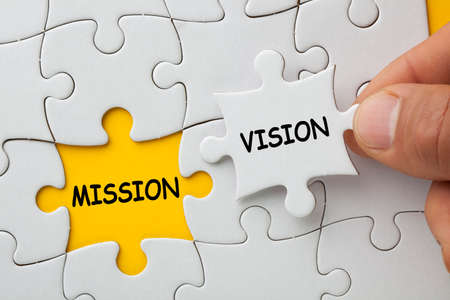 Hand holding missing jigsaw puzzle piece with word vision, covering text mission.