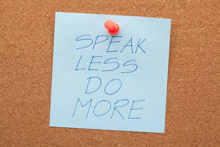 Speak less do more phrase on note pinned on cork board.