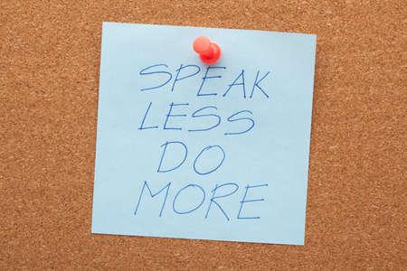 Speak less do more phrase on note pinned on cork board.