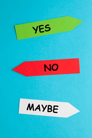 The words Yes, No and Maybe in paper arrows on blue background. Business concept. 免版税图像
