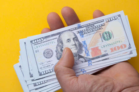 Hand holding 100 dollar bills on a yellow background. Concept saving money investment shopping pay and people richness. 免版税图像