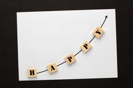 The word happy with directional arrow written on cubes shape wooden blocks.