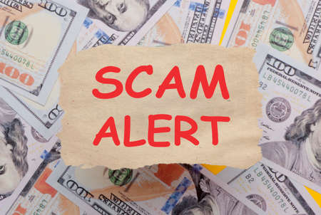 Background of dollar bills with scam alert text written with marker on old torn paper. Selective focus