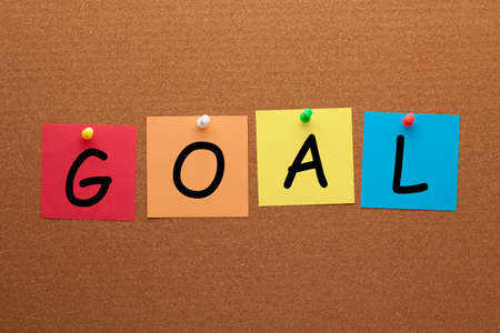 The word goal on colorful notes pinned on cork board