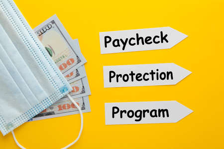 Paycheck Protection Program (PPP) text on paper arrow with  medical mask and  hundred dollar bills. The concept of epidemic Фото со стока