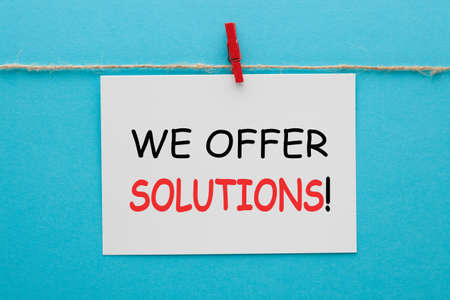 We offer solutions text on white tag hanging on a rope on blue background. Фото со стока