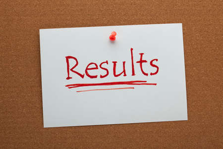 The word results written on white paper sheet pinned on cork board.