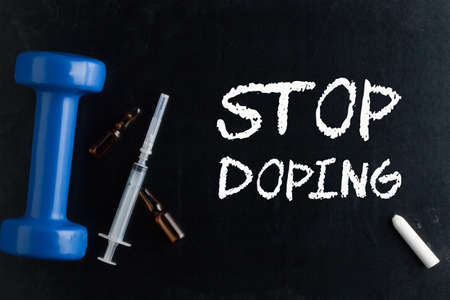 Stop Doping written with chalk and dumbbell, syringe and ampoule on blackboard.