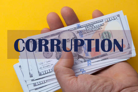 The word corruption over hand holding 100 dollar bills on a yellow background.