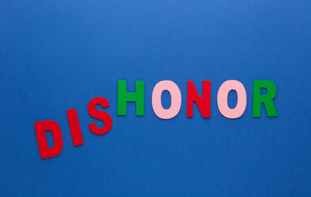 Words dishonor transformed to honor made of colorful alphabet letters on blue background.
