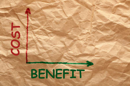 Cost and benefit graph on a wrinkled paper. Business concept.