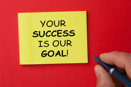 Man hand writing your success is our goal with pen on note. Business concept. Фото со стока