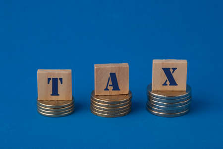Tax concept with wooden block on step stacked coins on blue background. Business and finance concept.