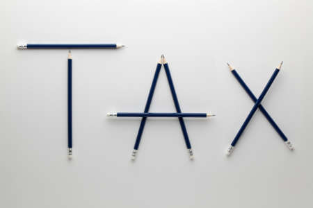 The word tax made of pencil on white background. Business and finance concept.
