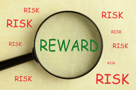 Magnifying glass over the word  risk and reward concept background.