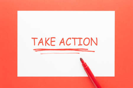 Take Action written on white paper sheet and red marker. Фото со стока