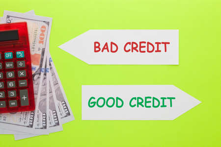 Good credit versus bad credit written on paper arrow with hundred dollar bills and calculator. Business concept.