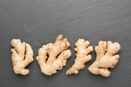 Ginger root on a dark stone background. Top view.